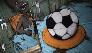 Brazilian artist Paulo Ito talks on his mobile phone next to graffiti he painted referencing the 2014 World Cup, on the door of a public schoolhouse in Sao Paulo. (Photo by Nacho Doce, Reuters)